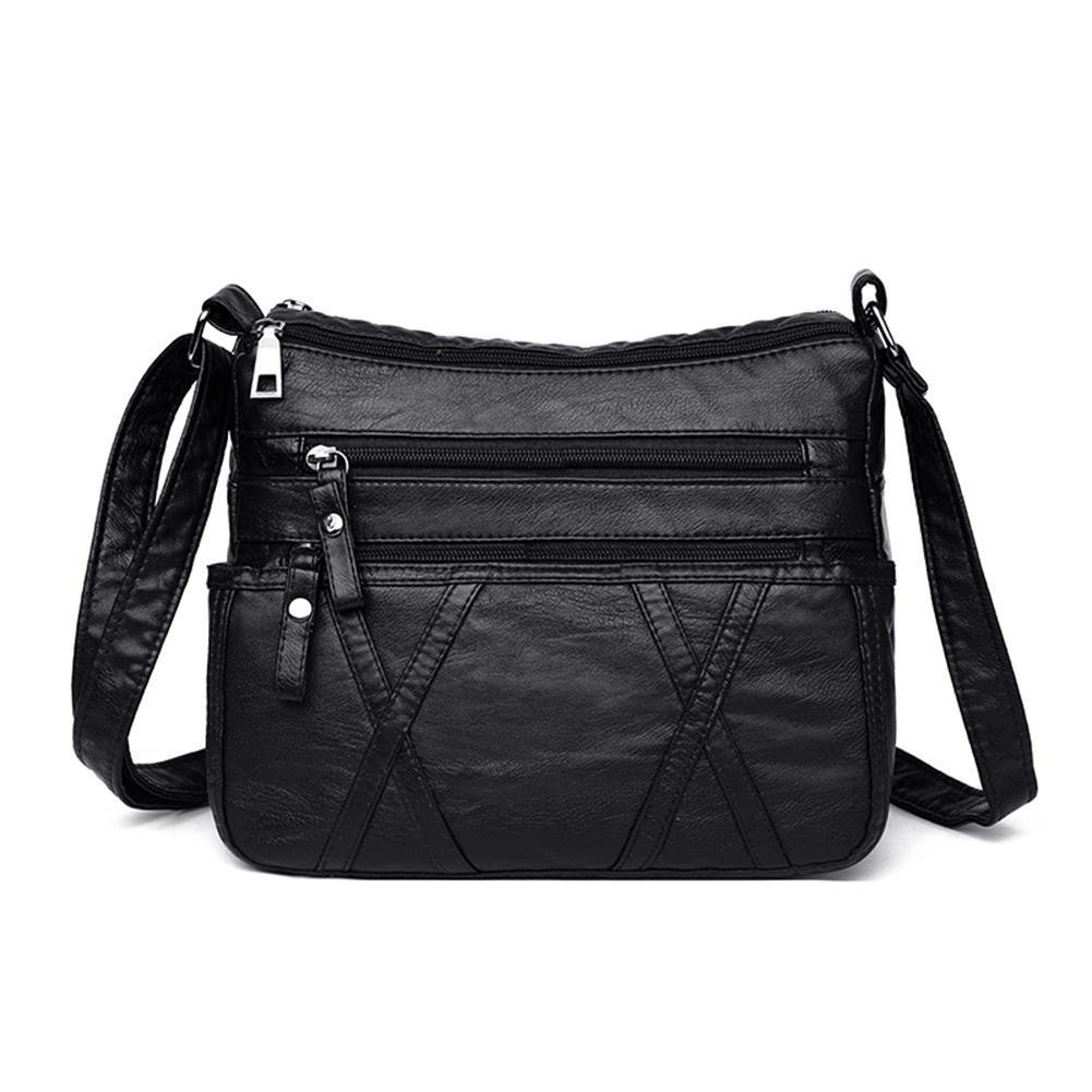Женская небольшая кожаная сумка с ремнем через плечо и отсеками на молнии фото